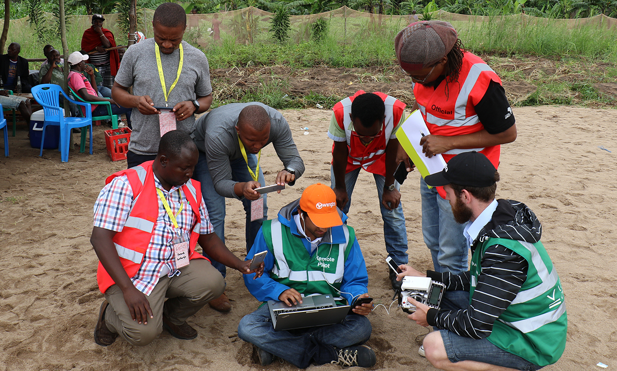 At the LVC launch area, safety-crew members and Juma community leaders gathered around two members of the Wingtra team who were monitoring their drone's flight.