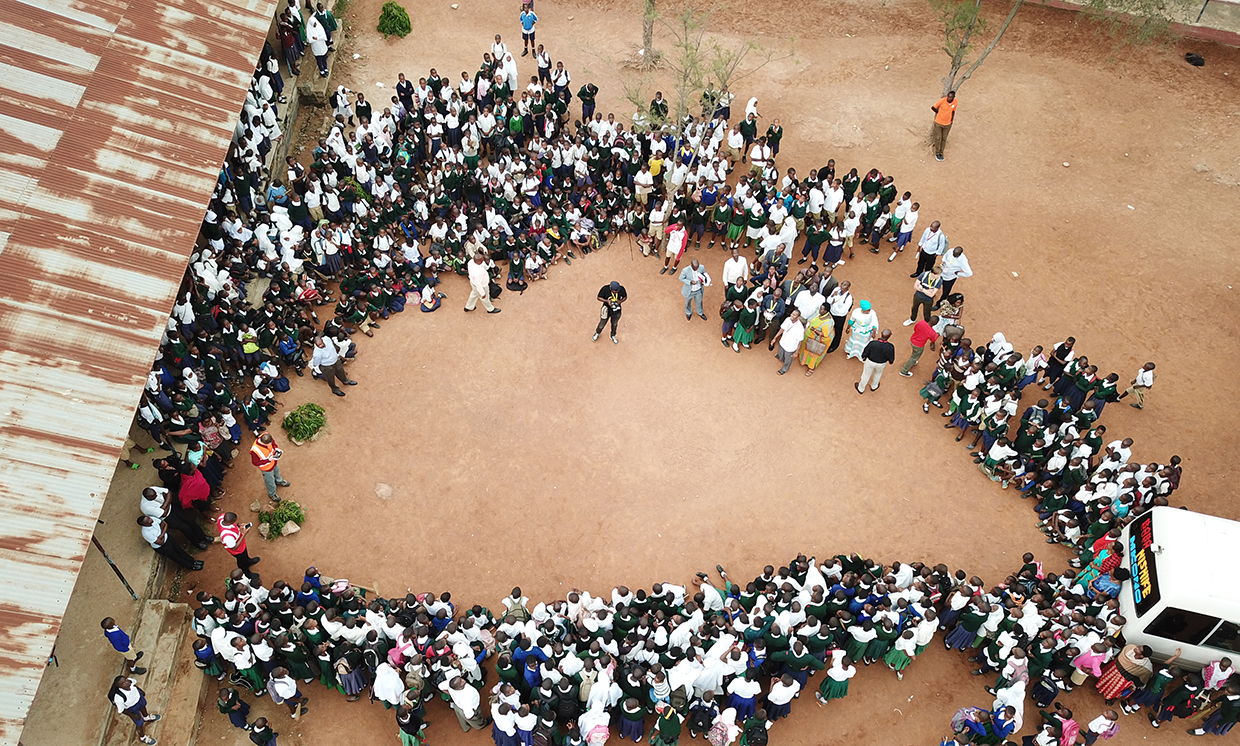 Aerial drone photo of a crowd of students listening to Tanzania Flying Labs' Leka Tingitana.