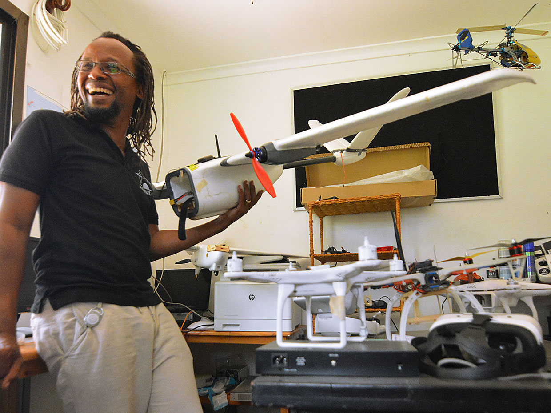Freddie Mbuya showing drone parts in his workshop.